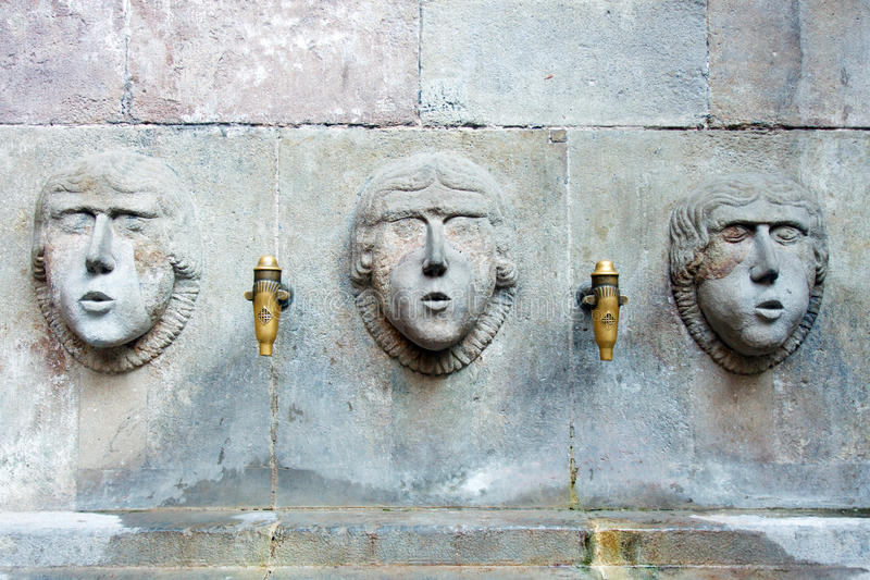 Ornate fountain. Carved faces in an ornate water fountain in Barcelona, Spain stock photos