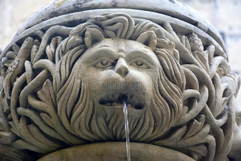 Ornate fountain depicting lion head. Ornate fountain depicting lion portrait with water streaming from lion's mouth royalty free stock photos