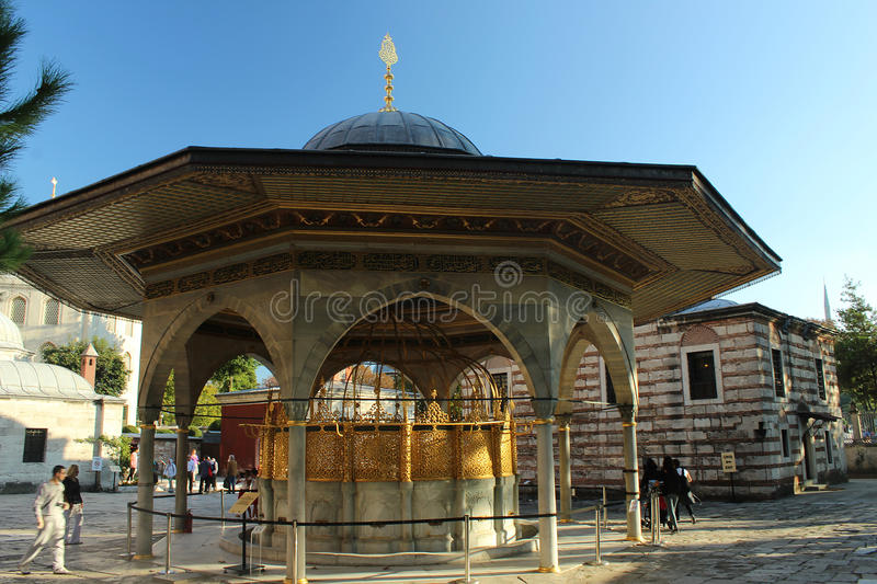 Ornate fountain. Istanbul, Turkey - September 17, 2015: Hagia Sophia in Sultanahmet district, Istanbul, Turkey. Tourists are walking around ornate fountain stock images