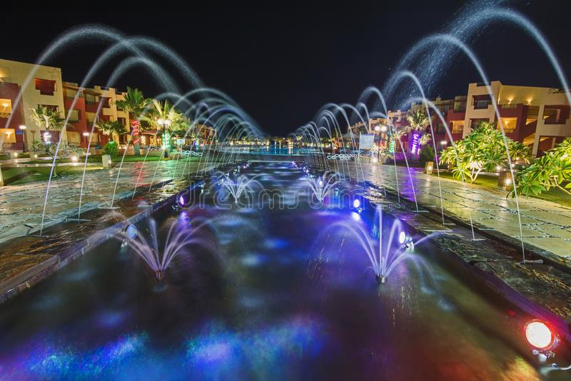 Ornate fountain lit up at night in luxury hotel resort. Ornate fountain water feature lit up at night by large swimming pool in a luxury tropical hotel resort stock photos