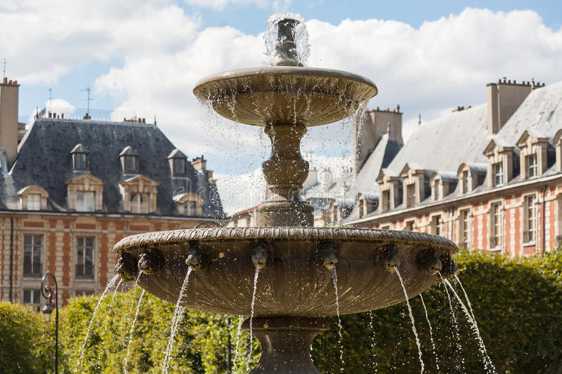Ornate fountain in Place des Vosges in Paris. Ornate fountain in Places du Vosges in Paris and beautiful buildings behind royalty free stock photos