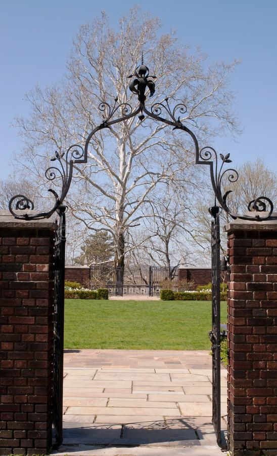 An ornate gate leading into a garden royalty free stock photography