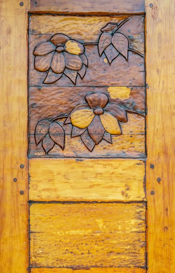 Ornate hand carved heavy old varnished wooden door with Dogwood Flower design. royalty free stock photography