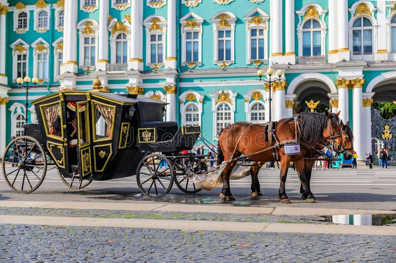 Ornate horse carriage awaiting tourist in front of the Winter Palace - Hermitage on Palace Square in Saint Petersburg, Russia. Saint Petersburg, Russia stock image