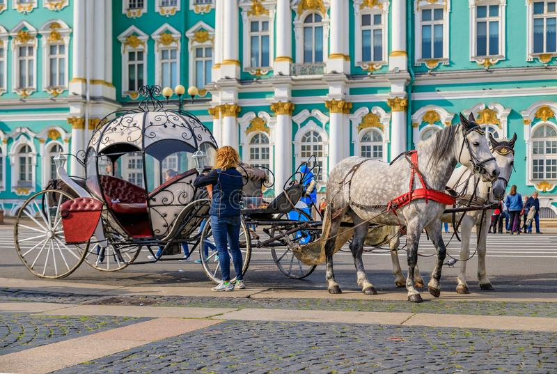 Ornate horse carriage awaiting tourist in front of the Winter Palace - Hermitage on Palace Square in Saint Petersburg, Russia. Saint Petersburg, Russia royalty free stock image
