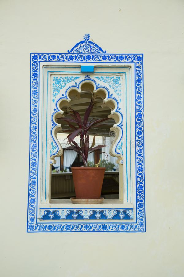 Ornate Indian Window Decor with Plant. Beautiful, ornate deep blue design surrounds a cut out Indian Rajput style window scalloped edges which in turn surrounds royalty free stock photography
