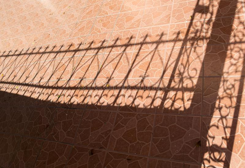 Tile floor and iron fence shadow royalty free stock photos