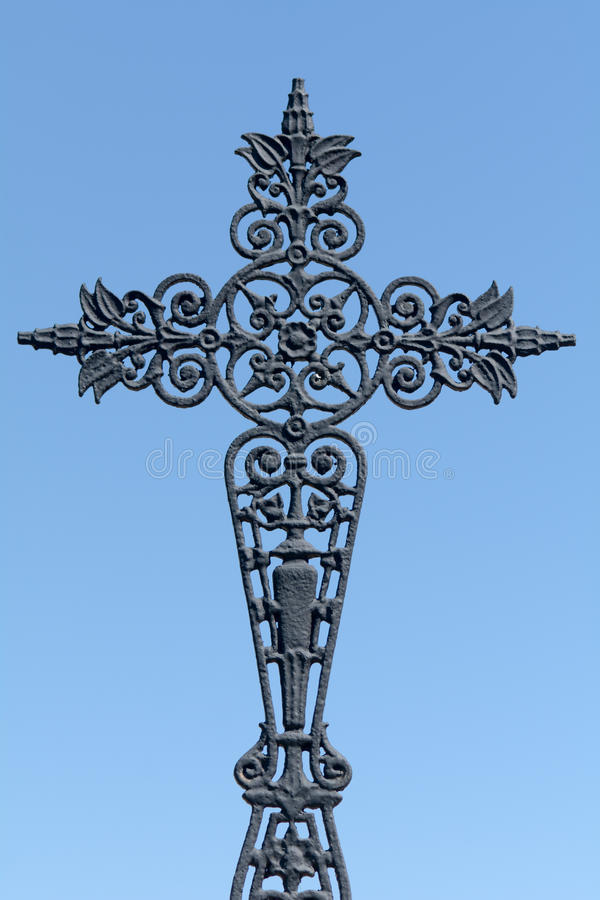 Ornate metal grave cross in cemetery royalty free stock image