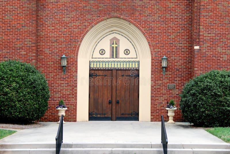 Ornate oak church doors brick walls hedges stock image