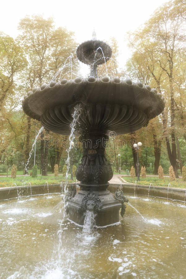 Ornate, Sculpted Fountain in a Public Park. Water flows from level to level of an ornate, sculpted, multitier fountain in a beautiful, public garden park stock photo