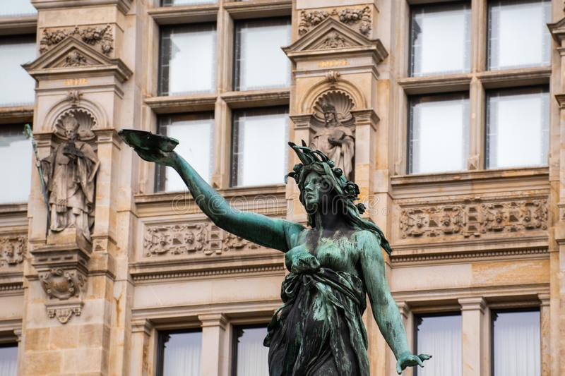 Ornate statue in fountain with old building in background. Ornate statue in fountain with old building in the background royalty free stock photo