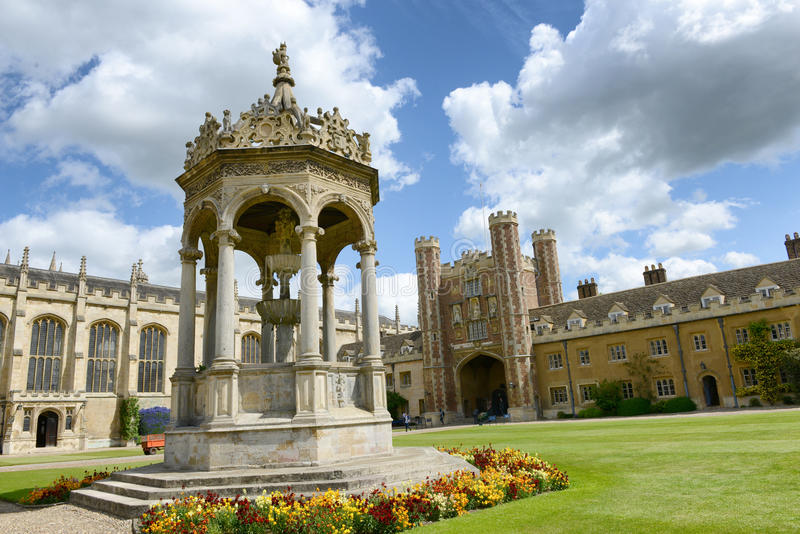 Ornate stone fountain in the Great Court. At Trinity College, Cambridge University, Cambridge, UK standig in manicured lawns with the Great Gate visible behind royalty free stock photography