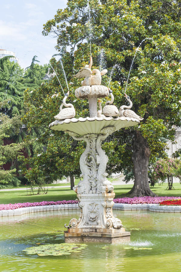 Ornate swan styled fountain in formal garden. Ornate carved swan fountain in pond of formal gardens at Dolmabahce Palace Istanbul Turkey royalty free stock photos