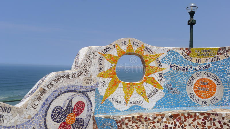 Ornate tiled bench in Miraflores district of Lima. Scenical view of an ornate tiled bench, a lamppost, the Pacific Ocean and the horizon over water. The photo stock image