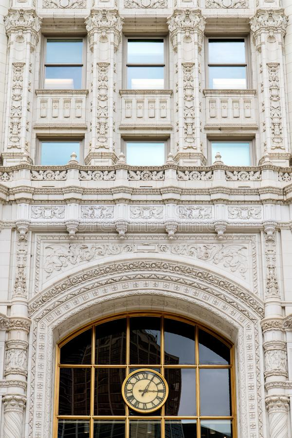 Free Ornate White Facade Of An Historic Building With A Clock With Roman Numerals And A Large Window Reflecting Modern Office Buildings Stock Photos - 158379093