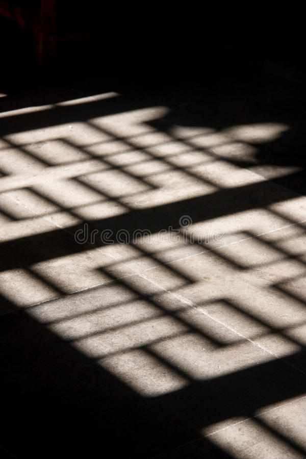 Ornate wooden screen casts interesting shadow on stone floor. royalty free stock image