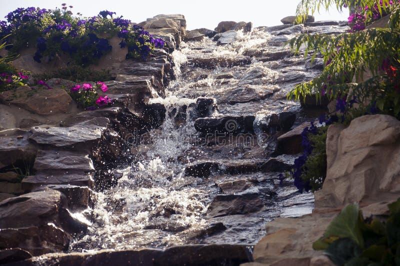 Ornated vattenfall i trädgårdträdgård med blommor arkivbild