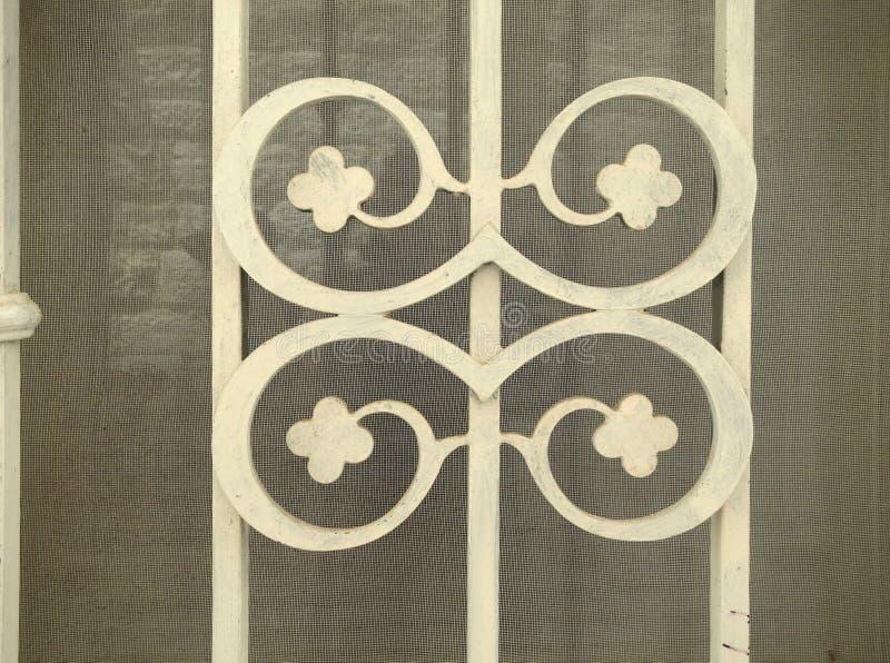 Ornement de fonte des clous de girofle sur les barres quatre protégeant une fenêtre photo stock