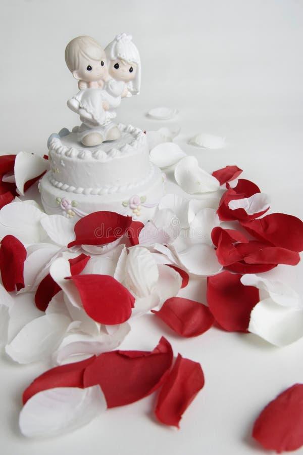 Ornement de la mariée de transport de marié entourée par les pétales roses photo libre de droits