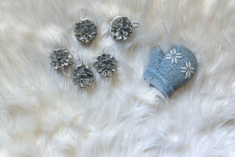 Ornement de Noël de cinq cônes de pin argenté sur un tissu blanc avec une bougie formée par gant bleu photo libre de droits