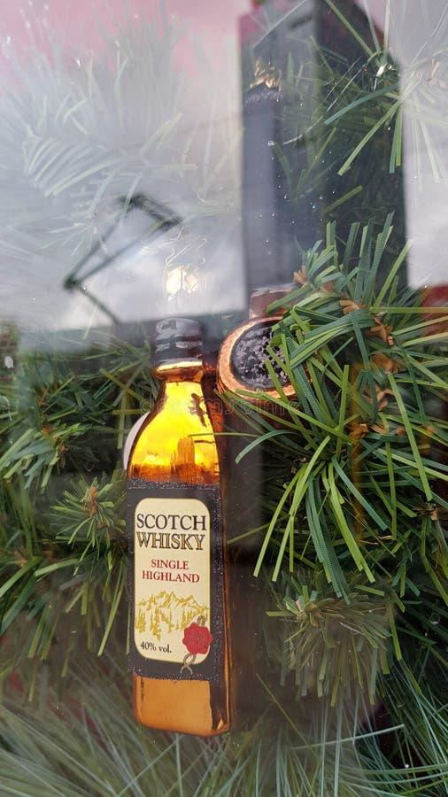 Ornement de Noël dans la forme du whisky écossais de bouteille d'alcool avec la réflexion abstraite dans le verre de fenêtre image libre de droits