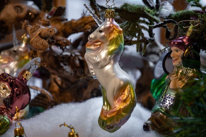 Ornement en verre handcrafted stupéfiant de Noël dans la forme de la licorne blanche avec la crinière d'arc-en-ciel et le klaxon  photographie stock libre de droits