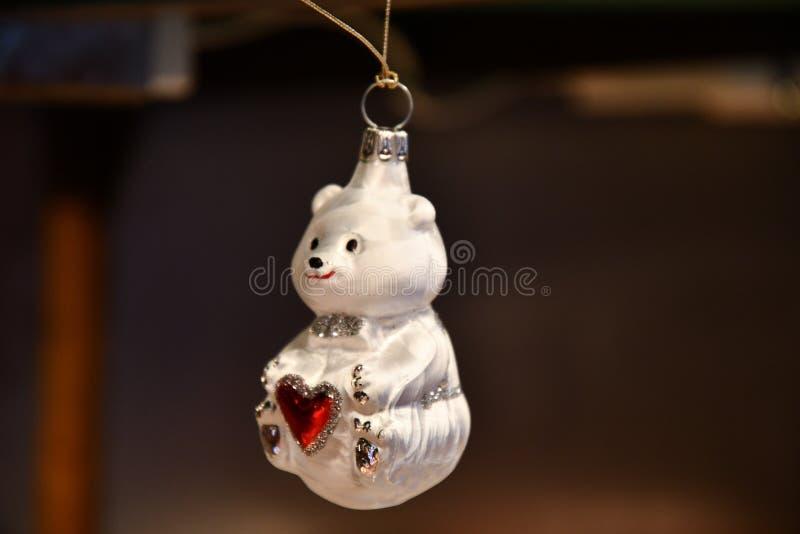 Ornement en verre mignon de Noël dans la forme de peu d'ours blanc de bébé avec le coeur rouge et les détails argentés de scintil image libre de droits