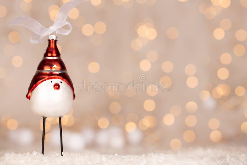 Ornement mignon d'oiseau de Noël avec le bokeh des lumières de Noël jaune et blanc images libres de droits