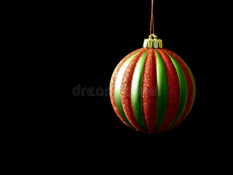 Ornement rouge et vert de Noël sur le noir images stock
