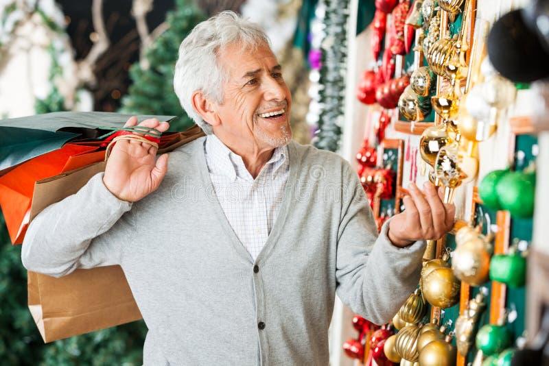 Ornements de achat de Noël d'homme supérieur au magasin image libre de droits
