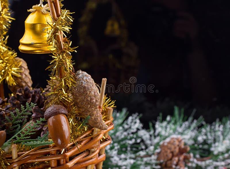 Ornements de Noël avec la guirlande des perles, des cônes de pin et des glands s'étendant dans un panier photographie stock