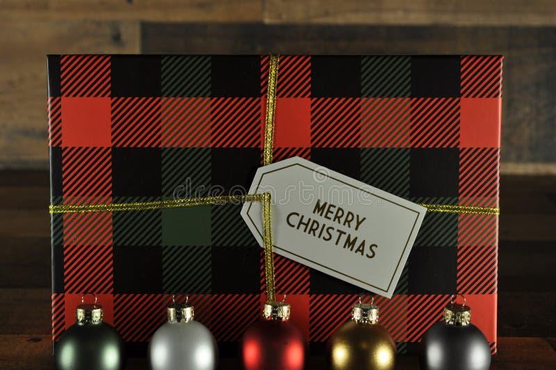 Ornements de Noël avec le boîte-cadeau de plaid derrière photo libre de droits