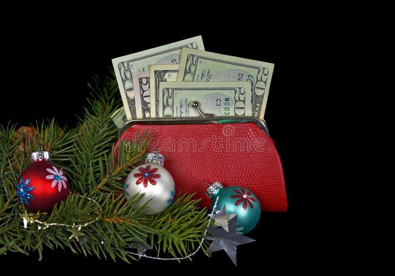 Ornements et argent de Noël dans la bourse photographie stock
