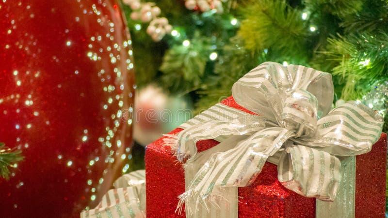 Ornements rouges et argentés de Noël dans la gauche du cadre avec le cadeau dans la droite du cadre images stock