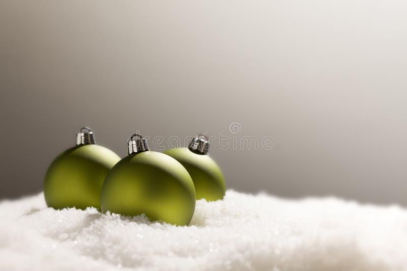 Ornements verts dramatiques de Noël sur la neige au-dessus de Grey Background photo stock