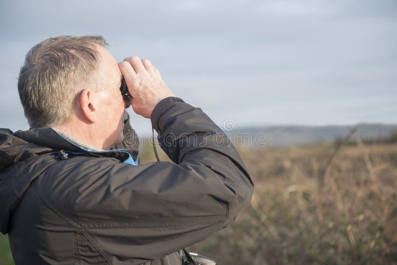 Ornitologia madura do homem, guardando um par de binóculos imagens de stock