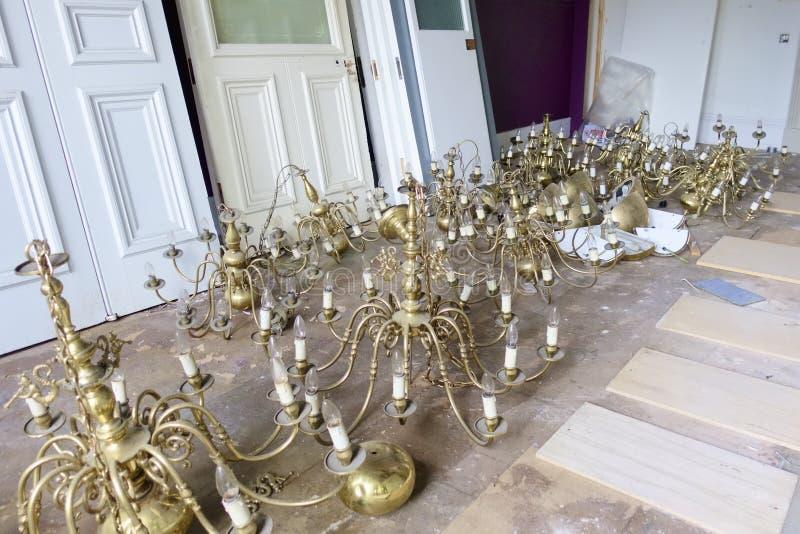 Oro antico delle luci del candeliere sul salvataggio del pavimento rimosso dal soffitto nel cantiere fotografia stock libera da diritti