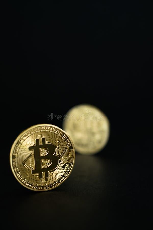 Oro Bitcoins físico en fondo negro imagenes de archivo