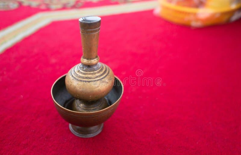 Oro d'ottone in un vaso disposto su un tappeto rosso immagine stock libera da diritti