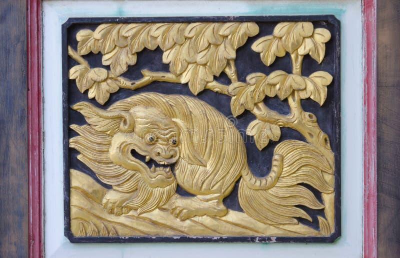 Oro del león, talla de madera adornada en templo fotografía de archivo