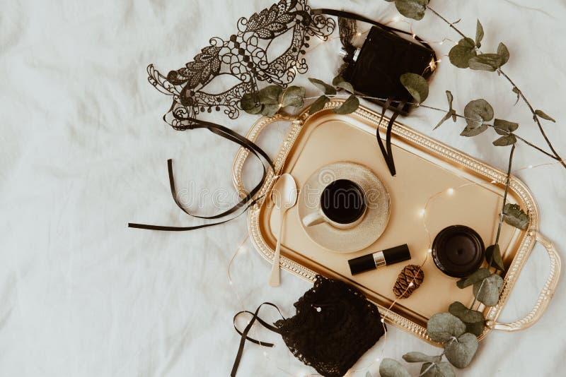 Oro di modo di vista superiore ed accessori neri Maschera, caffè, rossetto e biancheria del pizzo fotografia stock
