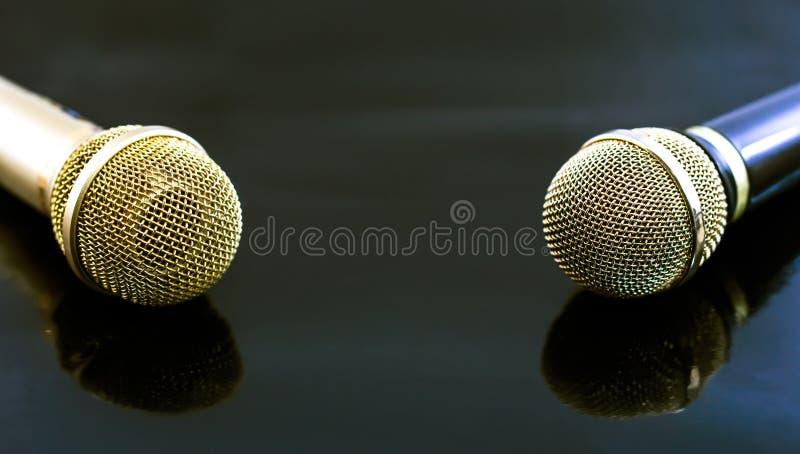 Oro e microfoni neri su fondo nero immagine stock libera da diritti