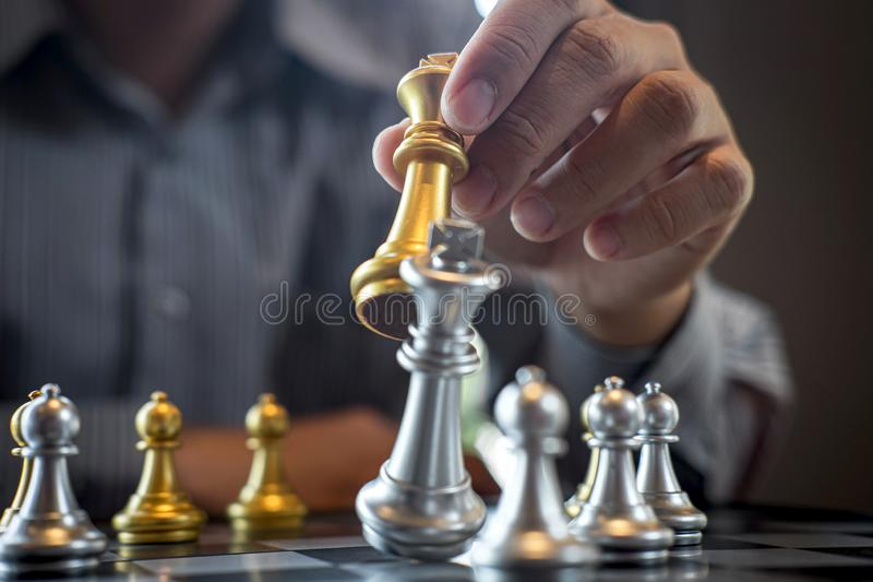Oro e scacchi d'argento con il giocatore, uomo d'affari intelligente che gioca la concorrenza del gioco di scacchi all'affare di  immagini stock libere da diritti