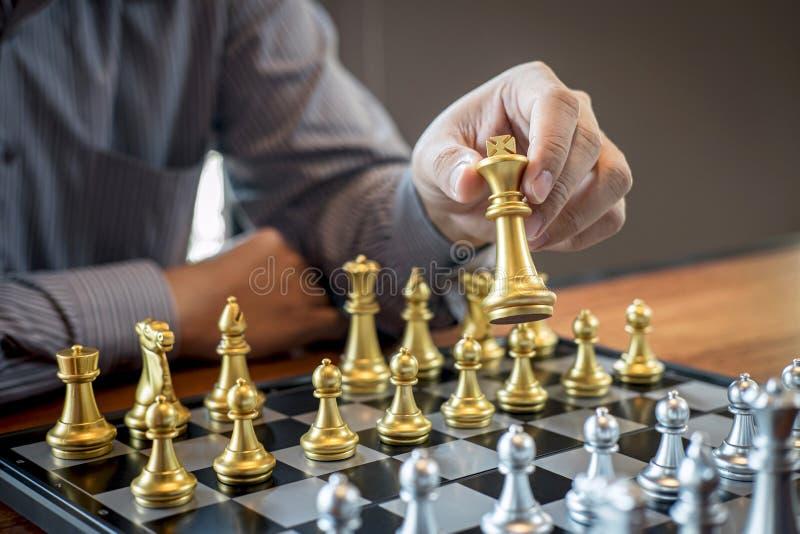 Oro e scacchi d'argento con il giocatore, uomo d'affari intelligente che gioca la concorrenza del gioco di scacchi all'affare di  fotografia stock