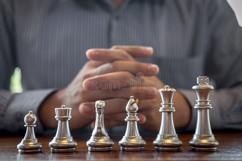 Oro e scacchi d'argento con il giocatore, uomo d'affari intelligente che gioca la concorrenza del gioco di scacchi all'affare di  immagine stock