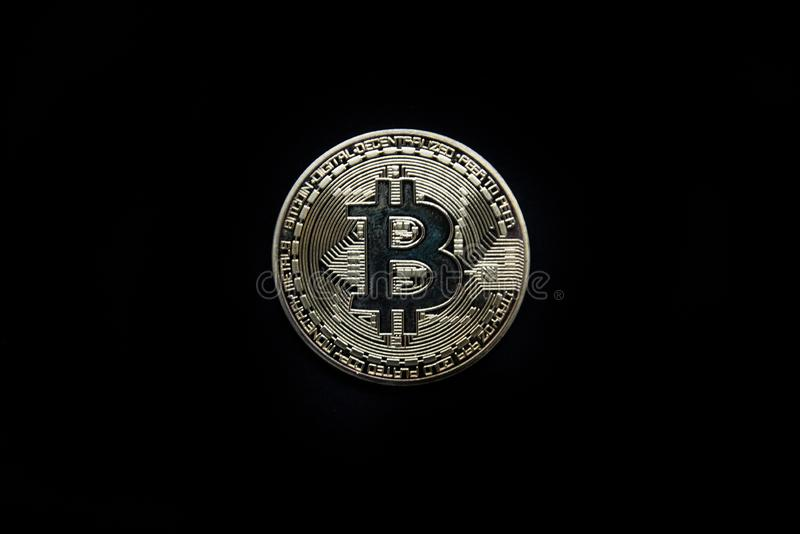 Oro físico Bitcoin aislado contra un fondo negro foto de archivo