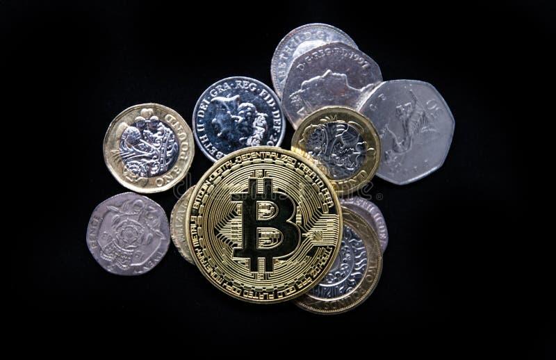 Oro físico Bitcoin que pone encima del dinero inglés viejo llano imágenes de archivo libres de regalías