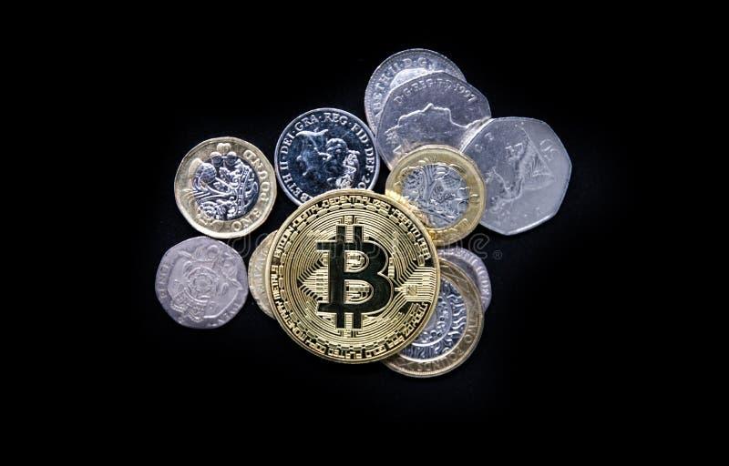 Oro físico Bitcoin que pone encima del dinero inglés viejo llano fotografía de archivo libre de regalías