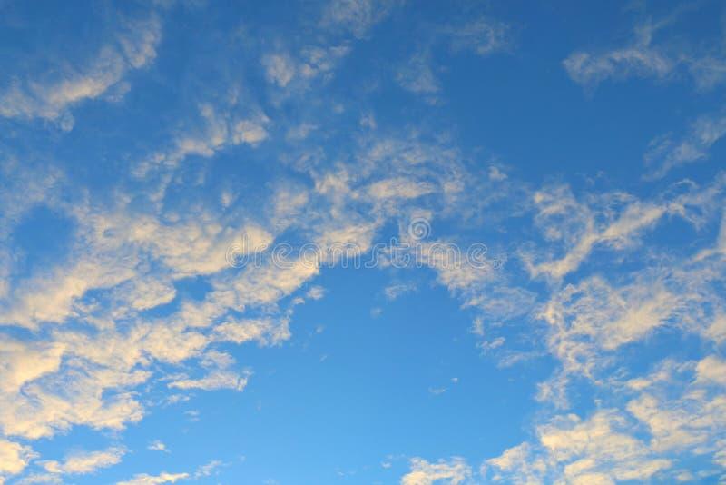 Oro giallo di chiaro colore morbido del sole sul fondo blu del cielo di sera della nuvola immagine stock