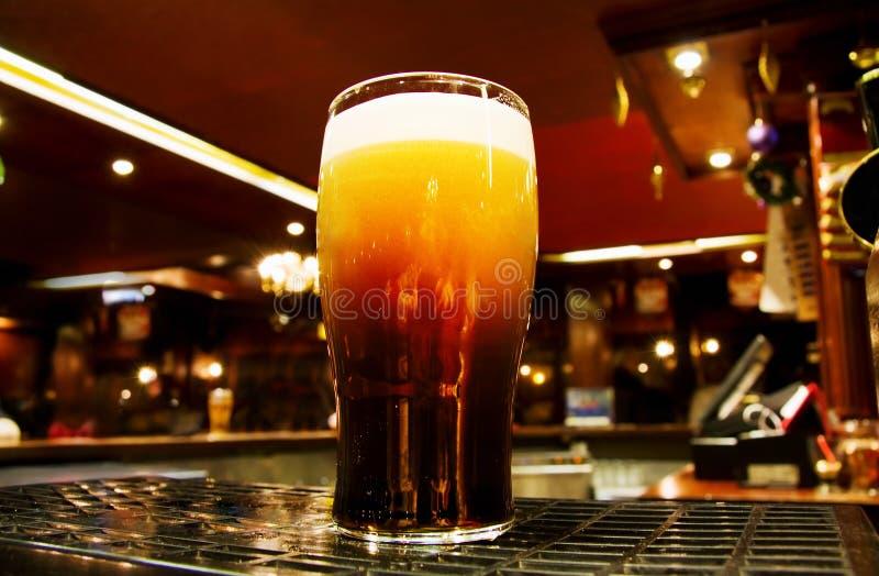 Oro irlandese - birra nera all'interno di un pub di Dublino fotografia stock libera da diritti
